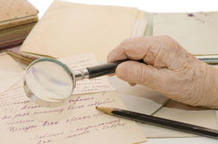 Old hand with a magnifier on letters Royalty Free Stock Photos