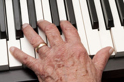 Old Hand on Piano Keys. Hand of an older man playing the piano Royalty Free Stock Photography