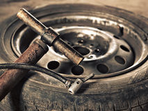 Old hand-pump and car wheel close-up Royalty Free Stock Image
