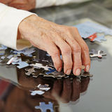 Old hand reaching for jigsaw puzzle. Old hand with wrinkles reaching for a jigsaw puzzle piece Royalty Free Stock Photos