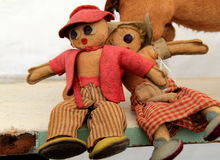 Old hand sewn dolls dressed in checkered clothing Stock Image