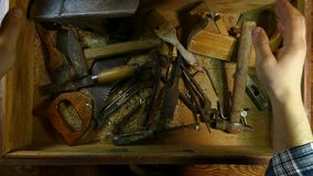 Old hand tool in a wooden chest. Retro tool. Rusty pliers, hammer, file, saw. Old wooden tool box.. Old hand tool in a wooden chest. Retro tool. Rusty pliers stock video footage