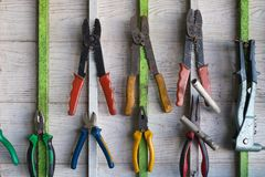 Old hand tools hanging on wall in workshop or auto service garage, many tool shelf against a wall, car mechanic concept. Old hand tools hanging on wall in royalty free stock photos