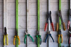 Old hand tools hanging on wall in workshop or auto service garage, many tool shelf against a wall, car mechanic concept. Old hand tools hanging on wall in royalty free stock photo