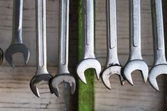 Old hand tools hanging on wall in workshop or auto service garage, many tool shelf against a wall, car mechanic concept. Old hand tools hanging on wall in stock images