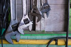 Old hand tools hanging on wall in workshop or auto service garage, many tool shelf against a wall, car mechanic concept. Old hand tools hanging on wall in stock photography