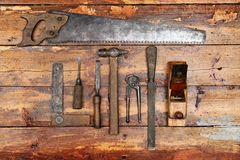 Old hand tools on wooden background. Old vintage hand tools on wooden background royalty free stock images