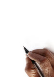 Old hand writing. An old wrinkled hand holding a pen against a white paper background Stock Images
