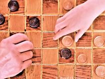 Old hand and young hand playing checkers stock photos