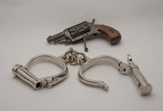 Old handcuffs and revolver Stock Photo