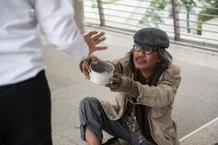 Old homeless man ask for money in city. Old handicapped homeless man ask for money while Businessman raise hand to refuse giving money. Poverty and social issue stock photography