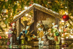 Old handmade nativity scene. In front of a christmas tree royalty free stock images
