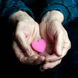 Old hands. Pink heart in the old hands royalty free stock photos