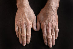Old hands. Old wrinkled hands on dark fabric royalty free stock images