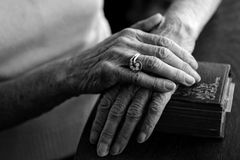 Old Hands. Old Woman's Hands on Her Bible Wearing Her Vintage Ring royalty free stock photography