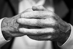 Old Hands. A grainy, black and white close up of old, weathered hands clasped together royalty free stock image