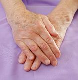 Old hands on bed Royalty Free Stock Photos