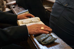 Old hands with Bible and glasses. In a church Royalty Free Stock Image