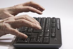 Old hands on the black keyboard Stock Image