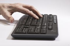 Old hands on the black keyboard Royalty Free Stock Photo