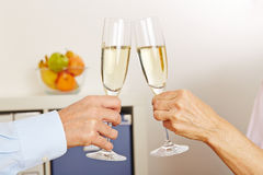 Old hands clinking champagne glasses Stock Photo