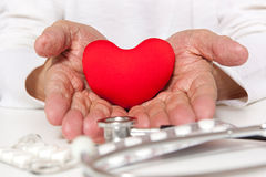 Old hands of the elderly giving a red heart royalty free stock photo
