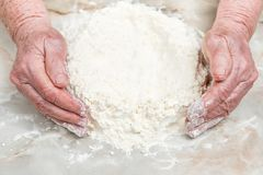 Old hands in flour on table. Old woman hands make a hill of flour on the table, close-up Stock Images