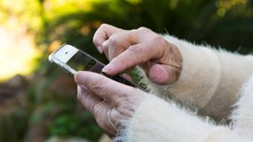 Old hands of grandmother holding a mobile phone in the garden house. Old hands of grandmother holding a mobile phone. Grandma using and looking at smart phone in royalty free stock image