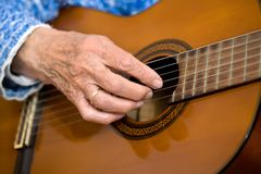 Old hands on guitar Royalty Free Stock Photo