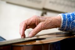 Old hands on guitar. Closeup of an elderly woman playing the guitar stock image