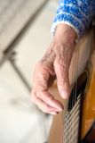 Old hands on guitar Stock Photography