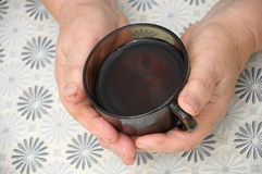 Old Hands Holding cap of tea Stock Photography