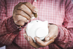 Old hands holding piggy bank and coins Royalty Free Stock Photos