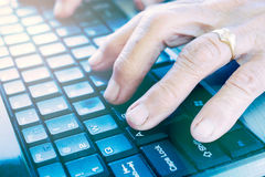 Old hands on keyboard Stock Photography