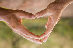 Old hands makesymbol of Heart stock photo
