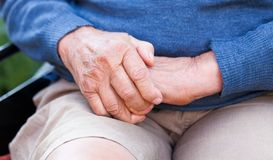 Old hands. Old man sitting in wheelchair, warming up his hands Royalty Free Stock Photos