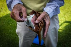 Old hands with a moneybag. In it, bank notes in the wallet stock photos