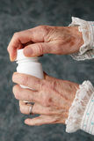 Old hands opening pill bottle Royalty Free Stock Photo
