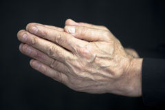 Old hands praying. Old man praying hands on black background stock images
