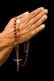 Old hands praying. An old asian woman holds her hands in prayer with a rosary Stock Image
