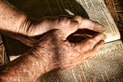 Old Hands Praying. Wrinkled praying hands folded above a bible with dramatic lighting Royalty Free Stock Image