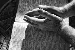 Old Hands Praying. Wrinkled praying hands folded above a bible with dramatic lighting in black and white Royalty Free Stock Photos