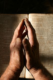 Old Hands Praying. Wrinkled praying hands folded above a bible with dramatic lighting Stock Photo
