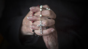 Old hands praying and holding a rosary Royalty Free Stock Photography