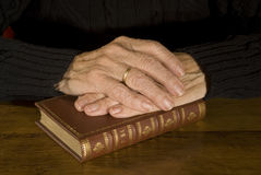 Old hands resting at antique bible Royalty Free Stock Photo
