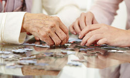 Old hands solving jigsaw puzzle. In a nursing home Royalty Free Stock Photos