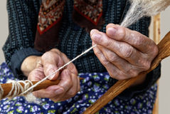 Old hands spinning wool. Royalty Free Stock Photos