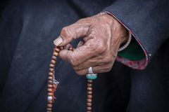 Old Tibetan woman holding buddhist rosary in Hemis monastery, Ladakh, India. Hand and rosary, close up royalty free stock photo