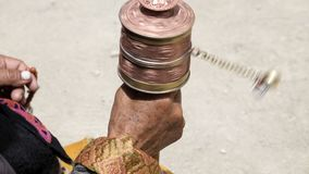 Old hands of a Tibetan woman holding prayer buddhist wheel at a Hemis monastery, Leh district, Ladakh, Jammu and Kashmir, north In Royalty Free Stock Photo
