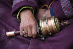 Old hands of a Tibetan woman holding prayer buddhist wheel at a Hemis monastery, Leh district, Ladakh, Jammu and Kashmir, north In Royalty Free Stock Images